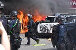 A police car burns as another one is seen destroyed during a protest over the death of George Floyd Saturday, May 30, 2020, in Los Angeles. Floyd died in police custody on May 25 in Minneapolis. (AP Photo/Mark J. Terrill)