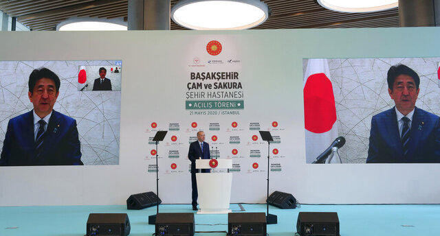 In this photo provided by the Turkish Presidency, Turkey's President Recep Tayyip Erdogan speaks to Japanese Prime Minister Shinzo Abe via video link, during the inauguration ceremony for Basaksehir Pine and Sakura City Hospital, in Istanbul, Thursday, May 21, 2020. Abe has called for international cooperation against the new coronavirus, saying any drug or vaccine developed against the virus must be made
