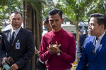 Pro-democracy activist Panupong Jadnok, also known as Mike Rayong, center, gestures as he arrives at criminal courthouse for hearing to determine whether he has violated his bail conditions in Bangkok, Thailand, Thursday, Sept. 3, 2020. A Thai court considered Thursday whether to grant a police request to revoke the bail of two top leaders of the burgeoning anti-government protest movement who refuse to stop their public political activities. (AP Photo/Gemunu Amarasinghe)