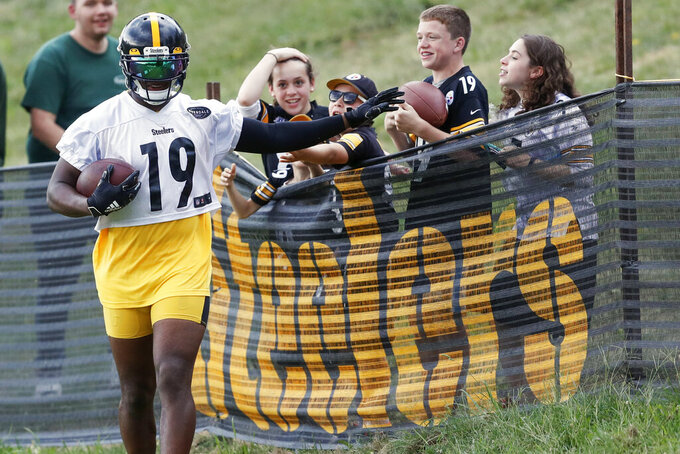 FILE - In this Thursday, Aug. 15, 2019, file photo, Pittsburgh Steelers wide receiver JuJu Smith-Schuster (19) talks with some young fans along the fence line after making a catch in drills during practice at NFL football training camp in Latrobe, Pa. The coronavirus pandemic forced the NFL to abandon, at least for 2020, the fading but still time-honored tradition of teams traveling to training camp. (AP Photo/Keith Srakocic, File)
