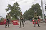 Indian paramilitary soldiers stand guard near a temporary check post on the road leading towards Independence Day parade venue during lockdown in Srinagar, Indian controlled Kashmir, Thursday, Aug. 15, 2019. Indian Prime Minister Narendra Modi says that stripping the disputed Kashmir region of its statehood and special constitutional provisions has helped unify the country. Modi gave the annual Independence Day address from the historic Red Fort in New Delhi as an unprecedented security lockdown kept people in Indian-administered Kashmir indoors for an eleventh day. (AP Photo/ Dar Yasin)