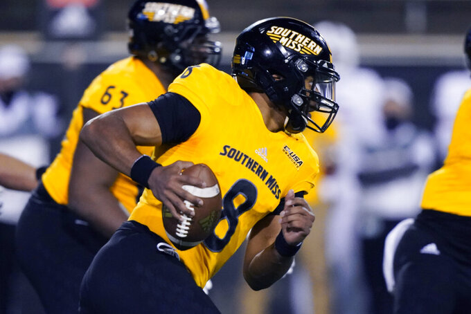 Southern Mississippi quarterback Trey Lowe (8) runs behind blockers during the second half of the team's NCAA college football game against Florida Atlantic, Thursday, Dec. 10, 2020, in Hattiesburg, Miss. (AP Photo/Rogelio V. Solis)