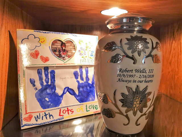 Robert Wells III's urn sits on a shelf in the St. Charles Parish home of his mother, Deborah Wells, in front of a card bearing hand prints made when he was 3-years-old. Deborah Wells penned a heartbreakingly raw obituary about her son's violent death. (Michelle Hunter/The Advocate via AP)