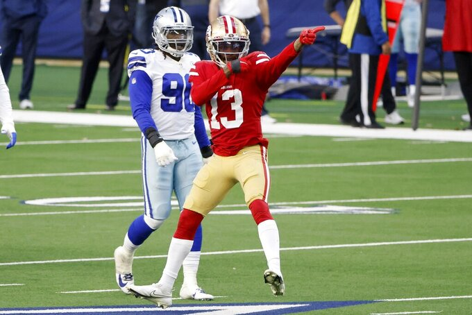 San Francisco 49ers wide receiver Richie James (13) celebrates catching a pass for a first down as Dallas Cowboys defensive end DeMarcus Lawrence (90) looks on in the second half of an NFL football game in Arlington, Texas, Sunday, Dec. 20, 2020. (AP Photo/Michael Ainsworth)