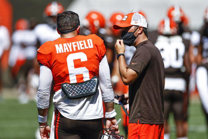 FILE - Cleveland Browns head coach Kevin Stefanski, right, talks with quarterback Baker Mayfield, left, during practice at the NFL football team's training facility Wednesday, Aug. 19, 2020, in Berea, Ohio. Teams with new coaches or new quarterbacks could limit their playbooks early in the season because they missed valuable practice time in the offseason due to the coronavirus shutdown. Mayfield is learning his third offense in three seasons. (AP Photo/Ron Schwane, File)