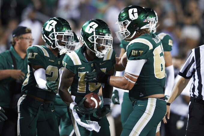 Charlotte defensive back Valerian Agbaw (16) is congratulated by teammates after recovering a fumble during the team's NCAA college football game against Duke on Friday, Sept. 3, 2021, in Charlotte, N.C. (AP Photo/Brian Westerholt)