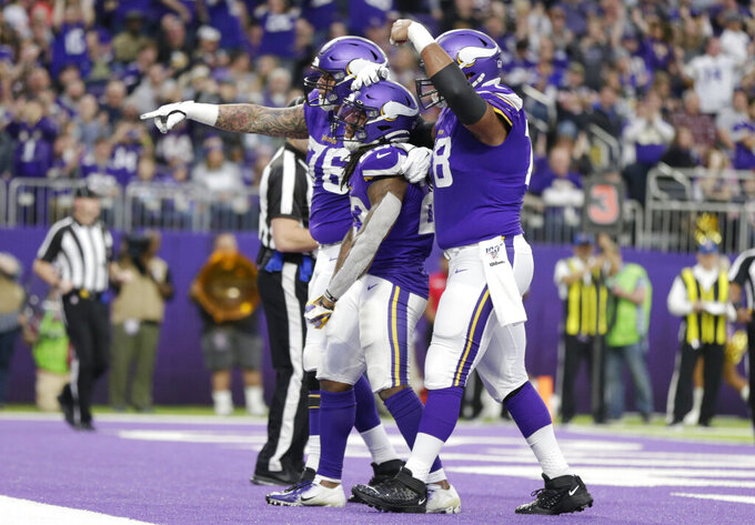 Minnesota Vikings running back Mike Boone, center, celebrates with teammates after scoring on a 1-yard touchdown run during the second half of an NFL football game against the Chicago Bears, Sunday, Dec. 29, 2019, in Minneapolis. (AP Photo/Andy Clayton-King)