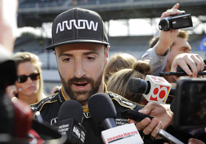 FILE - In this May 19, 2018, file photo, James Hinchcliffe, of Canada, talks with the media after failed to qualify for the Indianapolis 500 auto race, in Indianapolis. Chip Ganassi and Michael Andretti have joined Roger Penske in calling for guaranteed spots in the Indianapolis 500. The team owners argue their financial commitment to IndyCar is too steep to afford missing out on the biggest race of the year. (AP Photo/Darron Cummings, File)