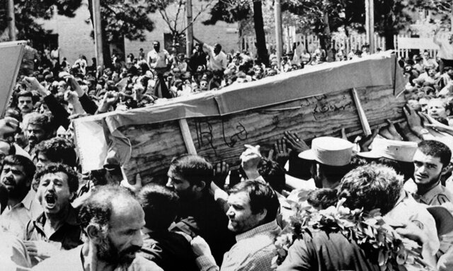 FILE - In this July 7, 1988 file photo, Iranian mourners carry one of 72 caskets to the Cemetery of Martyrs after attending a