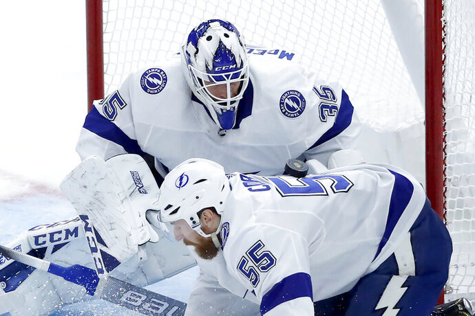 Tampa Bay Lightning goaltender Curtis McElhinney (35) keeps his eye on the puck landing on the back of Braydon Coburn, off a shot by Chicago Blackhawks' Jonathan Toews during the second period of an NHL hockey game Thursday, Nov. 21, 2019, in Chicago. (AP Photo/Charles Rex Arbogast)