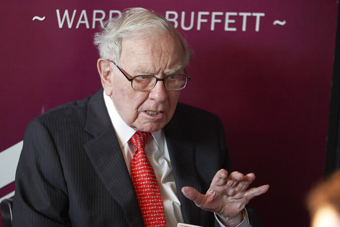 FILE - In this May 5, 2019, file photo Warren Buffett, Chairman and CEO of Berkshire Hathaway, gestures during a game of bridge following the annual Berkshire Hathaway shareholders meeting in Omaha, Neb. Three-quarters of the way through 2019, Buffett's conglomerate Berkshire Hathaway is trailing the renowned investor's favorite benchmark, the S&P 500, as it's done over the past decade.   (AP Photo/Nati Harnik, File)
