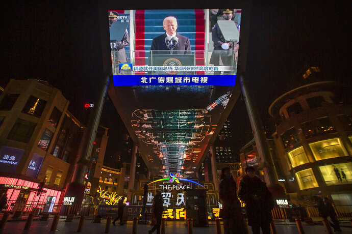 A large video screen shows a government news report about the inauguration of President Joe Biden at a shopping mall in Beijing, Thursday, Jan. 21, 2021. China has expressed hope the Biden administration will improve prospects for people of both countries and give a boost to relations after an especially rocky patch, while getting in a few final digs at former Trump officials. (AP Photo/Mark Schiefelbein)