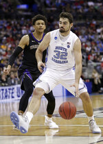 North Carolina's Luke Maye (32) drives against Washington's Matisse Thybulle, left, in the first half during a second-round men's college basketball game in the NCAA Tournament in Columbus, Ohio, Sunday, March 24, 2019. (AP Photo/Tony Dejak)