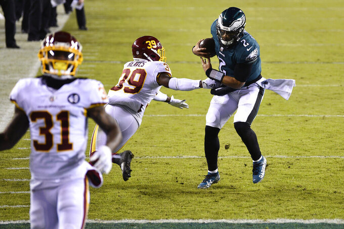 Philadelphia Eagles' Jalen Hurts (2) scrambles past Washington Football Team's Jeremy Reaves (39) for a touchdown during the first half of an NFL football game, Sunday, Jan. 3, 2021, in Philadelphia. (AP Photo/Derik Hamilton)