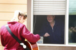 In this April 17, 2020, photo, Lowell Havener, right, a resident of Rising Mountains Assisted Living, smiles and sings along with music therapist Kirsten Wells in Bigfork, Mont. She played songs like