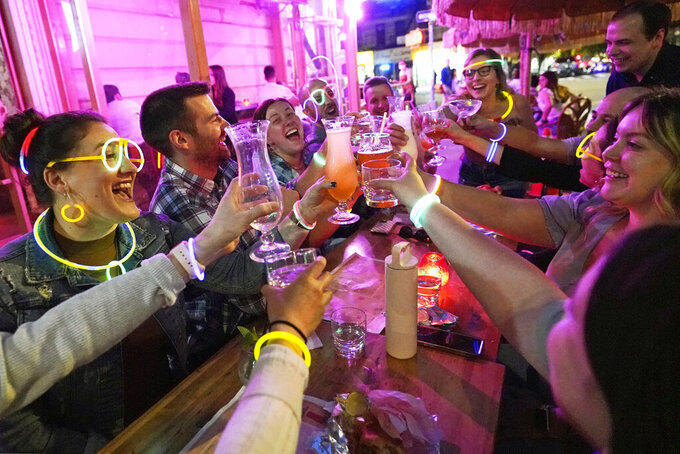 """FILE - In this May 17, 2021, file photo, Emily Baumgartner, left, and Luke Finley, second from left, join friends from their church group in a birthday toast to one of the members, upper right, during their weekly """"Monday Night Hang"""" gathering at the Tiki Bar on Manhattan's Upper West Side in New York. After a statewide midnight curfew on outdoor dining ended May 17, a similar indoor curfew for bars and restaurants ended on Monday, May 31 as coronavirus restrictions ease. (AP Photo/Kathy Willens, File)"""