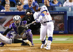 Los Angeles Dodgers' Russell Martin hits a three-run home run in front of Colorado Rockies catcher Tony Wolters and home plate umpire Dan Bellino during the seventh inning of a baseball game Tuesday, Sept. 3, 2019, in Los Angeles. (AP Photo/Mark J. Terrill)