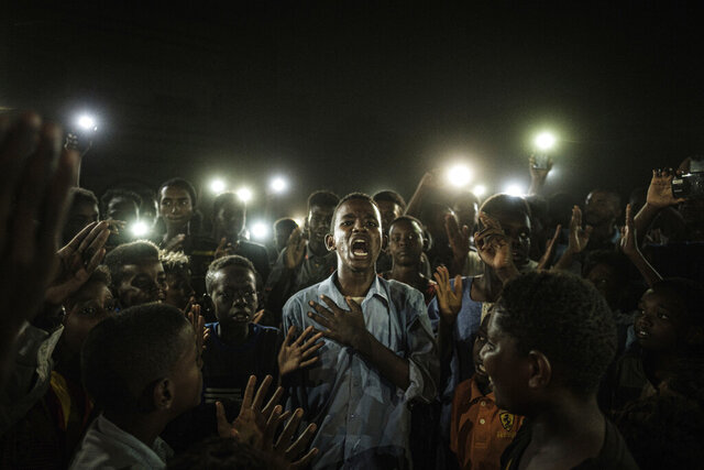 This image released by World Press Photo on Thursday April 16, 2020, taken by Yasuyoshi Chiba, Agence France-Presse, won the World Press Photo of the Year award, and the first prize in the General News Singles category, a young man, illuminated by mobile phones, recites protest poetry while demonstrators chant slogans calling for civilian rule, during a blackout in Khartoum, Sudan, on 19 June 2019. (Yasuyoshi Chiba, Agence France-Presse/World Press Photo via AP)