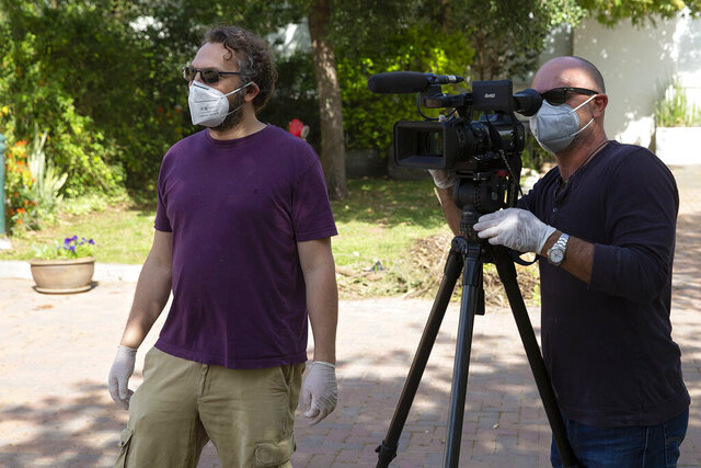 In this April 6, 2020, photo, Jerusalem correspondent Aron Heller, left, and cameraman Ami Ben-Tov interview a volunteer delivering food to the home of a doctor on the front lines of Israel's battle against the spread of the coronavirus. (AP Photo/Sebastian Scheiner)