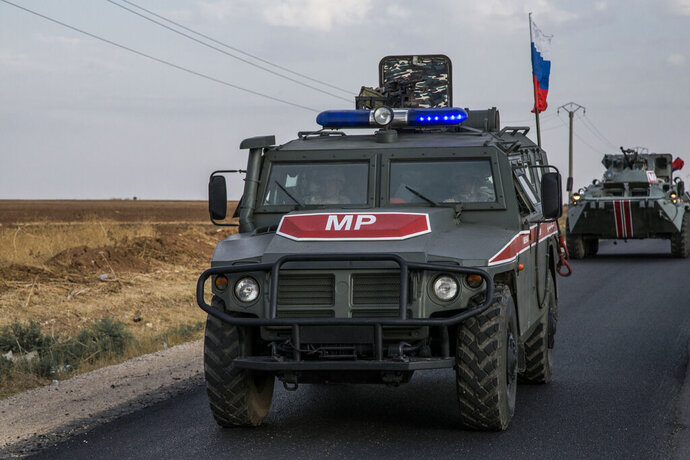 FILE - In this Oct. 24, 2019 file photo, Russian forces patrol near the city of Qamishli, north Syria. Russia's Defense Ministry spokesman Maj. Gen. Igor Konashenkov said Tuesday, Nov. 19, 2019, that the military was fielding additional military police units to carry out joint patrols with Turkey in Syria. (AP Photo/Baderkhan Ahmad, File)