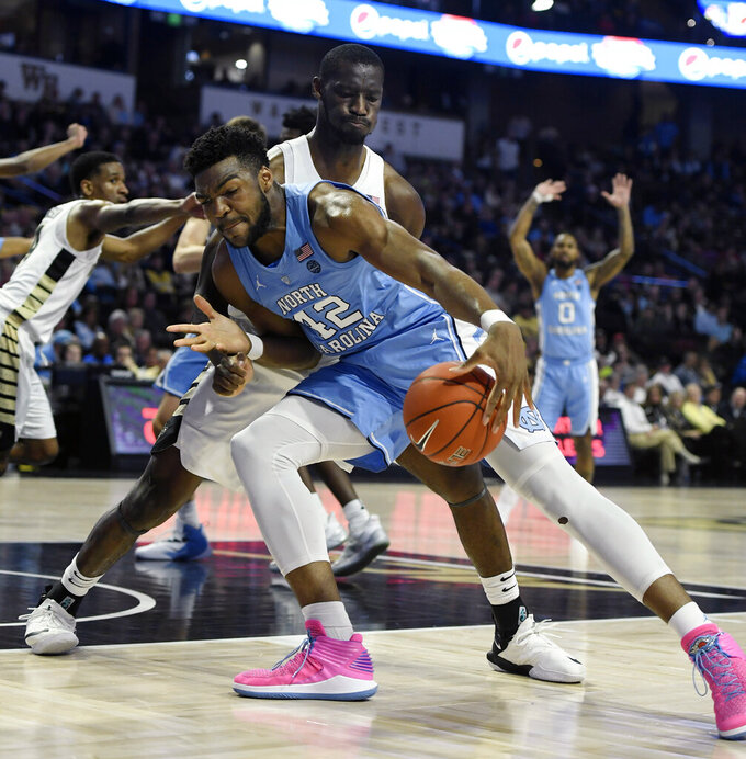 North Carolina's Brandon Huffman (42) drives to the basket as Wake Forest's Sunday Okeke (34) defends during the second half of an NCAA college basketball game in Winston-Salem, N.C., Saturday, Feb 16, 2019. (AP Photo/Woody Marshall)