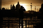 A man shoots photos as a golden sunset lights up Venice Sunday, , Italy, Sunday, Nov. 17, 2019, just hours after an exceptional 1.5 meter tide receded from nearby St. Mark's Square. It was the third flood topping 1.5 meters this week, following Tuesday's 1.87-meter flood which was the worst in 53 years. In background is Chiesa della Salute church, in Venice, Italy. (AP Photo/Luca Bruno)