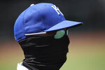 Kansas City Royals bench coach Pedro Grifol wears a mask as he watches baseball practice at Kauffman Stadium on Thursday, July 9, 2020, in Kansas City, Mo. (AP Photo/Charlie Riedel)