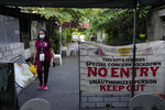 A village officer walks along a street in lockdown due to a COVID-19 case in Quezon city, Philippines on Thursday, Sept. 9, 2021. Officials say the virus has hit an orphanage and infected almost 100 children. (AP Photo/Aaron Favila)