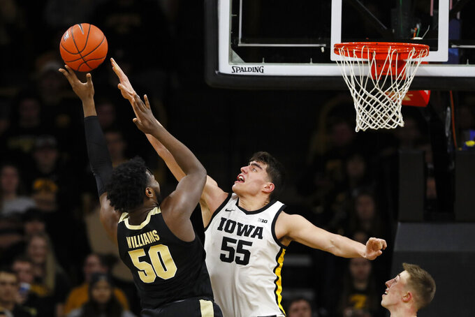 Purdue forward Trevion Williams shoots over Iowa center Luka Garza, right, during the second half of an NCAA college basketball game Tuesday, March 3, 2020, in Iowa City, Iowa. Purdue won 77-68. (AP Photo/Charlie Neibergall)