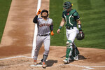 San Francisco Giants' Chadwick Tromp, left, celebrates after hitting a two-run home run next to Oakland Athletics catcher Sean Murphy during the third inning of a baseball game in Oakland, Calif., Sunday, Sept. 20, 2020. (AP Photo/Jeff Chiu)