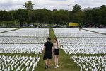 """People visit artist Suzanne Brennan Firstenberg's """"In America: Remember,"""" a temporary art installation made up of white flags to commemorate Americans who have died of COVID-19, on the National Mall in Washington, Tuesday, Sept. 21, 2021. (AP Photo/Patrick Semansky)"""