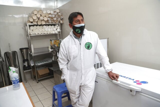 Tourist guide Efrain Valles, wearing a protective face mask, stands at his recently opened ice cream shop in Cuzco, Peru, Wednesday, Oct. 28, 2020. Valles, once one of the most sought-after tour guides in Cuzco high in Peru's Andes, is one of the 1.3 million people nationwide in a tourism industry devastated by the novel coronavirus and the measures imposed to fight its spread, including international travel restrictions. (AP Photo/Martin Mejia)