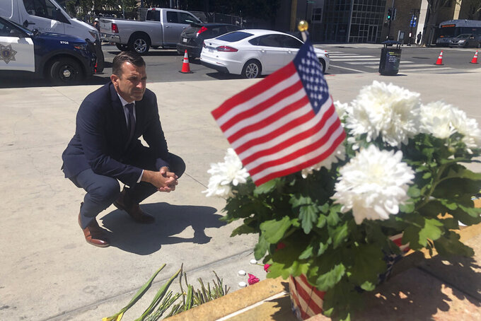 FILE - In this May 27, 2021, file photo, San Jose Mayor Sam Liccardo stops to view a makeshift memorial for the rail yard shooting victims in front of City Hall in San Jose, Calif. San Jose officials passed a new gun law, that requires gun owners to carry liability insurance and pay a fee to cover taxpayers' cost associated with gun violence. The City Council unanimously approved the new law Tuesday, June 29, 2021, less than a month after a disgruntled employee fatally shot nine of his co-workers and then himself at a rail yard in San Jose, according to police. (AP Photo/Haven Daley, File)