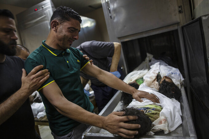 A Palestinian relative mourns over the bodies of four young brothers from the Tanani family who were found under the rubble of a destroyed house following Israeli airstrikes in Beit Lahiya, northern Gaza Strip, Friday, May 14, 2021. (AP Photo/Khalil Hamra)