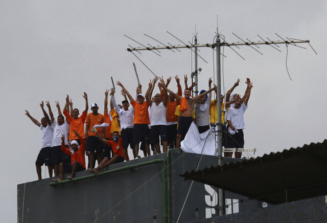 Inmates at the Puraquequara prison stand on a water tower as they protest against bad conditions and restrictions on family visits put in place to curb the spread of the new coronavirus, in Manaus, Brazil, Saturday, May 2, 2020. (AP Photo/Edmar Barros)