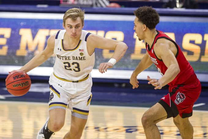 Notre Dame's Dane Goodwin (23) drives in next to North Carolina State's Jericole Hellems during the first half of an NCAA college basketball game Wednesday, March 3, 2021, in South Bend, Ind. (AP Photo/Robert Franklin)