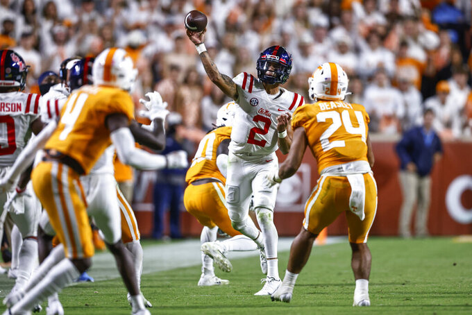 Mississippi quarterback Matt Corral (2) throws to a receiver as he's defended by Tennessee linebacker Aaron Beasley (24) during the second half of an NCAA college football game Saturday, Oct. 16, 2021, in Knoxville, Tenn. Mississippi won 31-26. (AP Photo/Wade Payne)