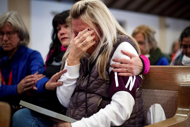 FILE - In this Nov. 18, 2018, file photo, Laura Martin mourns her father, TK Huff, who died during the Camp Fire, during a vigil in Chico, Calif. A scathing grand jury indictment unsealed Tuesday, June 16, 2020, into a Northern California wildfire that killed 85 people found that Pacific Gas & Electric officials repeatedly ignored warnings about its failing power lines, performed inadequate inspections to focus on profits and refused to learn from past catastrophes. Those who died were mostly elderly or disabled, the oldest 99 years old and the youngest 20. Their remains were found in showers and bathtubs, clutching a beloved photograph, cuddling pets, trapped in getaway cars and even seeking safety under a vehicle. TK Huff of the nearby town of Concow was found outside his home, 10 feet (3 meters) from his wheelchair. Evidence suggested the 71-year-old tried to drag himself away to escape the fire, the report said. (AP Photo/Noah Berger, Pool, File)