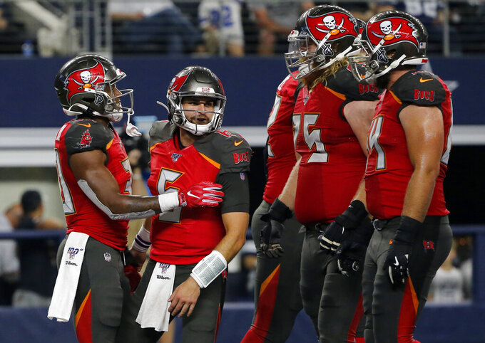 CORRECTS PLAYER NEXT TO ANDERSON TO VINCENT TESTAVERDE, INSTEAD OF CAIRO SANTOS - Tampa Bay Buccaneers running back Bruce Anderson III, left, is congratulated by quarterback Vincent Testaverde (6) and others after carrying the ball for a touchdown during the second half of the team's preseason NFL football game against the Dallas Cowboys in Arlington, Texas, Thursday, Aug. 29, 2019. (AP Photo/Michael Ainsworth)