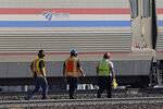 Workers walk past a baggage car, Monday, Sept. 27, 2021, from an Amtrak train that derailed Saturday, near Joplin, Mont., killing three people and injuring others. Federal investigators are seeking the cause of the derailment. (AP Photo/Ted S. Warren)