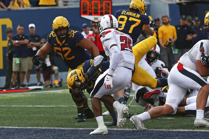 West Virginia running back Leddie Brown (4) is defended by Texas Tech defensive back Dadrion Taylor-Demerson (25) during the second half of an NCAA college football game in Morgantown, W.Va., Saturday, Oct. 2, 2021. (AP Photo/Kathleen Batten)