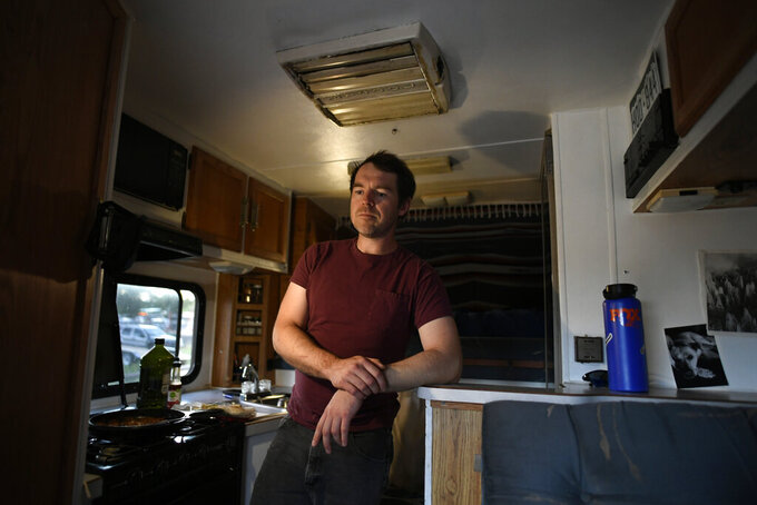 With battery powered lights the only thing available, Alex Eherenman, 35, reflects on life inside his camper on June 30, 2021 in Carbondale, Colo. The electrical system in his 1993 camper is shot and he doesn't have the money to fix it. Due to a wild housing market and various economic hardships at key points in their lives, many millennials feel like owning a home is unattainable.  (Helen H. Richardson /The Denver Post via AP)