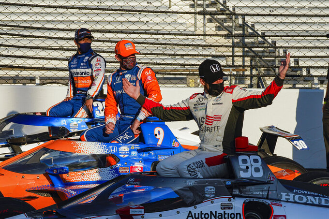 Marco Andretti, right, gestures to a late arrival for a front tow photo session, with Scott Dixon, of New Zealand, center and Takuma Sato, of Japan, for the Indianapolis 500 auto race at Indianapolis Motor Speedway in Indianapolis, Monday, Aug. 17, 2020. Andretti won the pole for Sunday's race. (AP Photo/Michael Conroy)