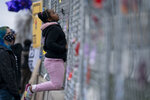Nevaeh Gibson inspects a two-layer fenced perimeter around the Brooklyn Center Police Department during a protest in response to the shooting death of Daunte Wright, Thursday, April 15, 2021, in Brooklyn Center, Minn. (AP Photo/John Minchillo)