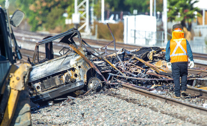 Heavy equipment begins to remove a burned motorhome from the railroad tracks following a collision with a commuter train in Santa Fe Springs, Calif., Friday, Nov. 22, 2019. Authorities say the collision occurred shortly after 5:30 a.m. Friday at an intersection in an industrial area of Santa Fe Springs. There were no immediate reports of injuries. All passengers on the Metrolink train were safely evacuated. (Mark Rightmire/The Orange County Register via AP)