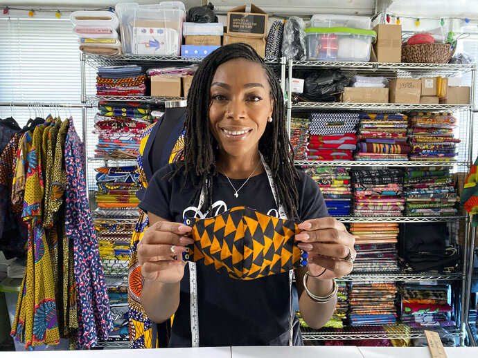 Iguehi James, an Oakland, Calif., fashion entrepreneur, holds a face mask she designed for her apparel company Love Iguehi on Tuesday, Sept. 15, 2020. She received a $5,000 grant from the Oakland African American Chamber of Commerce's
