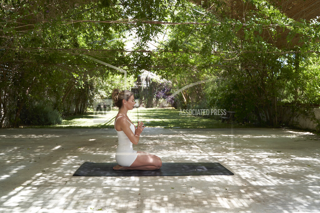 Woman with hand clasped meditating on exercise mat in garden