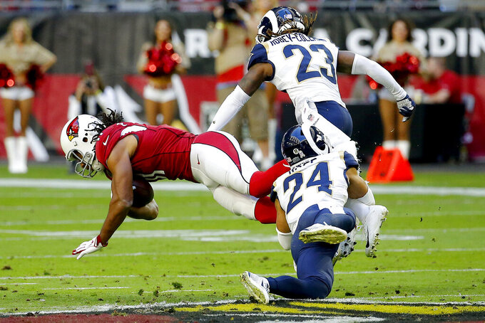 Arizona Cardinals wide receiver Larry Fitzgerald is tackled by Los Angeles Rams safety Taylor Rapp (24) during the first half of an NFL football game, Sunday, Dec. 1, 2019, in Glendale, Ariz. (AP Photo/Rick Scuteri)