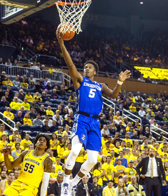 Creighton guard Ty-Shon Alexander (5) makes a layup, defended by Michigan guard Eli Brooks (55), in the first half of an NCAA college basketball game at Crisler Center in Ann Arbor, Mich., Tuesday, Nov. 12, 2019. (AP Photo/Tony Ding)