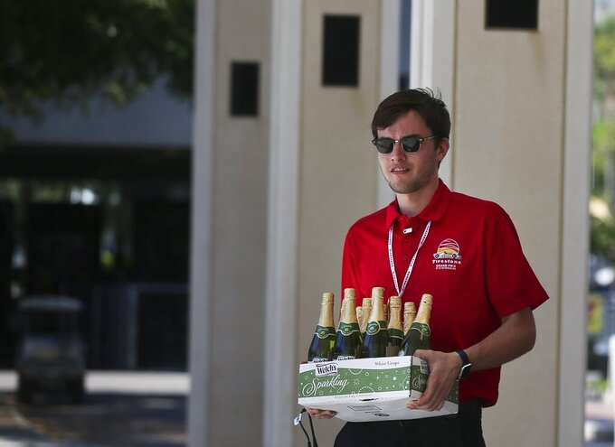 A Grand Prix staff member carries away the non alcoholic sparkling wine that would have been used for the Road to Indy series celebration after the news that the Grand Prix of St. Petersburg is canceled because of the coronavirus pandemic on Friday, March 13, 2020 in St. Petersburg, Fla. The IndyCar Series season opener was one of the last holdouts. Note: Due to the sound age of the majority of the drivers in that series, the bubbly is non alcoholic. (Dirk Shadd/Tampa Bay Times via AP)